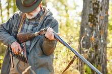 Senior Hunter Load Rifle And Going To Shoot. Man In Hunting Casual Clothes, Autumn Forest Background