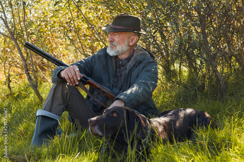 Fotografie, Tablou Hunter male with gun sit with faithful dog during hunting