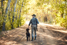Senior Hunter Holding Dog After Hunting On Ducks. Rear View On Hunter