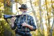 canvas print picture - Senior hunter on birds holding gun on shoulder, straighten hat, looking away. Forest background