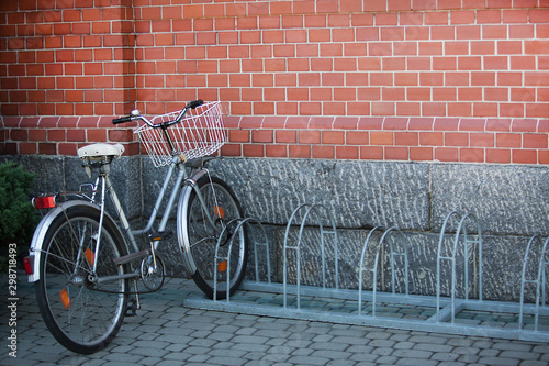 Bicycle, standing alone at the parking lot on a brick wall background