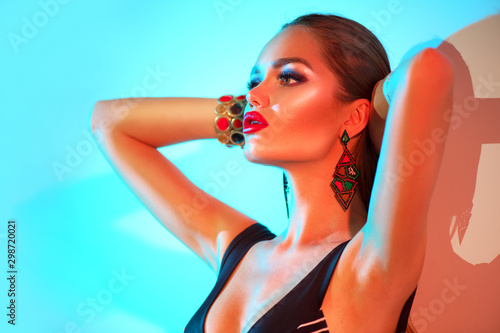 Fototapeta High Fashion model woman in colorful bright lights posing in swimsuit, portrait of beautiful sexy girl in swimwear, trendy accessories and make-up