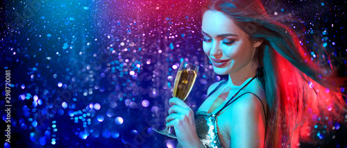Obraz Model girl with glass of champagne drinking and dancing at disco party, on holiday glowing blue with red background. Beauty woman, perfect fashion makeup. Christmas and New Year holiday celebration - fototapety do salonu