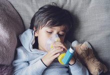 Poor Boy Tired From Chest Coughing Holding Inhaler Mask, Child Closing His Eyes While Using The Volumtic For Breathing Treatment,Tried Kid Having Asthma Allergy Using The Asthma Inhaler