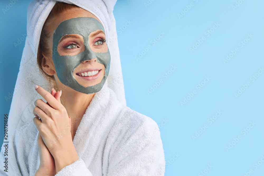 Fototapety, obrazy: Female with perfect skin and natural make-up. Wearing bathrobe and towel after bathing, using mask. Isolated over blue background