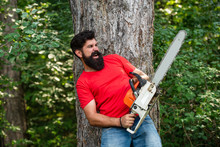 Lumberjack With Chainsaw On Forest Background. Man Doing Mans Job. Lumberjack With Chainsaw In His Hands. Lumberjack Concept. Firewood As A Renewable Energy Source.