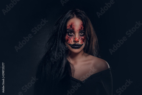 Fotografía Portrait of young woman in a role of evil scary clown at dark photo studio