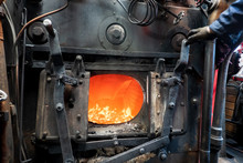An Open Door To The Furnace Of A Steam Engine. Coal Burns In The Furnace, An Orange Flame Is Visible. The Interior Is Inside A Steam Locomotive, There Is Metal Fittings. Background. Texture.
