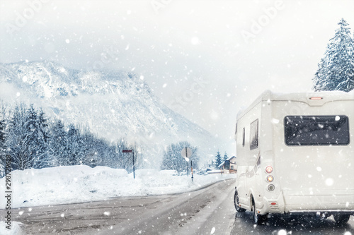 Canvas Print Caravan or campervan turning from road with beautiful mountain alpine landscape on background at cold winter season