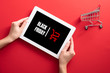 """canvas print picture - Hands holding tablet with sign """"Black friday"""" and shopping cart on screen over red background"""