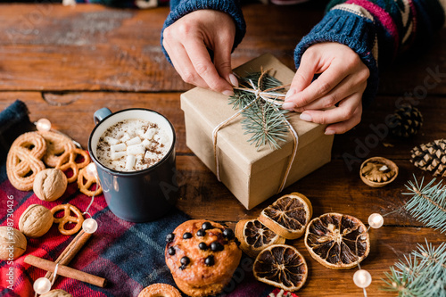 Montage in der Fensternische Brot Hands of girl making knot on top of wrapped giftbox surrounded by sweet food