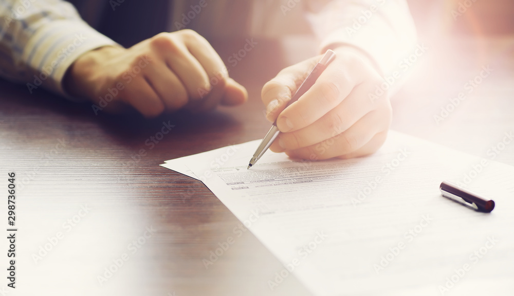Fototapeta Business meeting. A man signs a contract. Male hand with pen makes notes in the office.