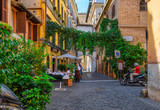 Fototapeta Uliczki - Cozy old street in Trastevere in Rome, Italy. Trastevere is rione of Rome, on west bank of Tiber in Rome. Architecture and landmark of Rome