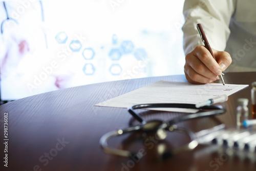Fotografía  A man signs a medical document