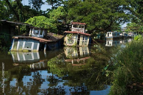 Photo Sunken house boats in Kerala backwater canal, Allappuzha, Alleppey, India
