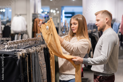 Obraz Young couple looking at yellow pants on hanger in clothing department - fototapety do salonu