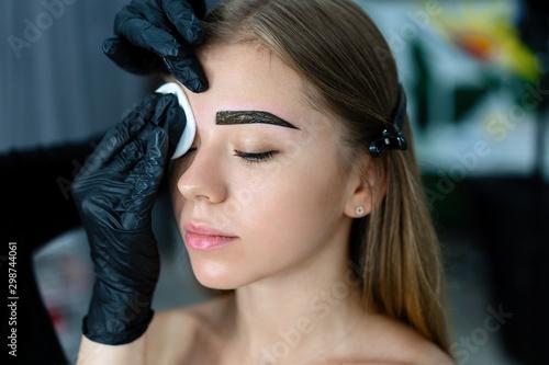 Young beautician caucasian girl holds model eyebrow correction Billede på lærred