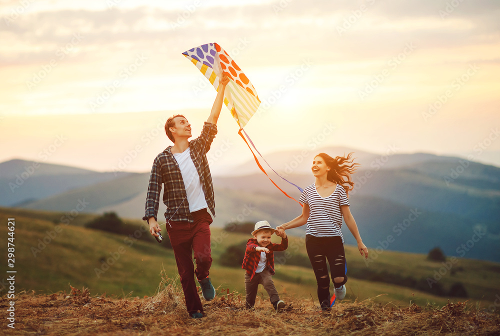 Fototapety, obrazy: Happy family father of mother and child son launch a kite on nature at sunset.