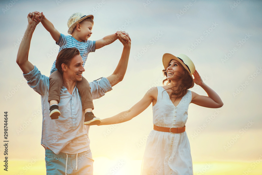 Fototapeta Happy family father of mother and child son  on nature at sunset.