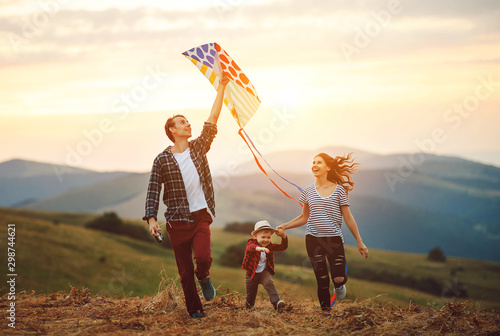 Fotografía  Happy family father of mother and child son launch a kite on nature at sunset