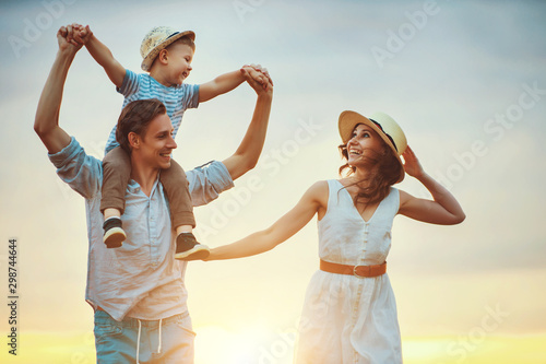 Fototapeta Happy family father of mother and child son  on nature at sunset. obraz