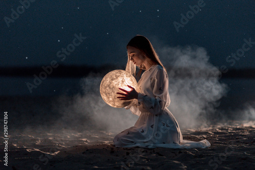 Beautiful young girl on a night beach with sand and stars holds the moon in her hands