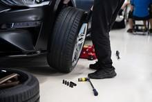 Mechanic Changing Wheel And Ti...