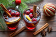 Mulled wine in glass mug with berries, cinnamon sticks and star anise on brown wood table