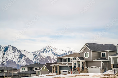 Winter neighborhood with homes viewed against snowy mountain and cloudy sky Fotobehang