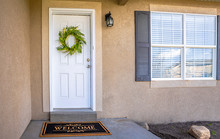 White Front Door With Green Le...
