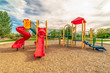 canvas print picture - Focus on empty childrens playground at a park with red slides and climbing bars