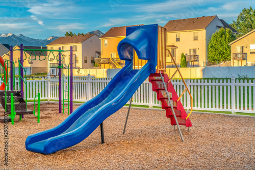 Fotografija Blue slide with red stairs at a playground against homes mountain and blue sky