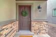 Front door of suburban home with green wreath