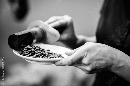 Keuken foto achterwand Cafe coffee beans are processed by coffee tools on a plate in black and white