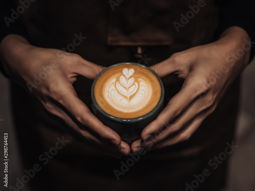 Wall Murals Cafe Coffee milk with a unique shape in the middle in a cup held by the hand