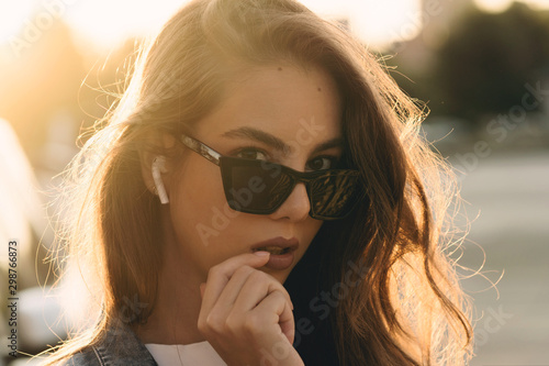 Poster de jardin Magasin de musique Dynamically young girl walks down the street. Hair fluttering in wind. Concept of street fashion. Young beautiful model in the city. Pretty woman listening music with wireless headphones in street
