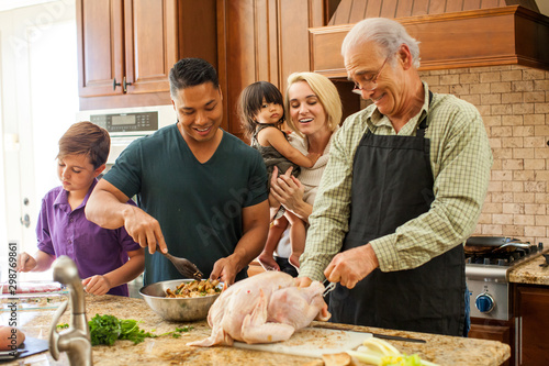 Mixed ethnicity  family having fun cooking in the kitchen Wallpaper Mural