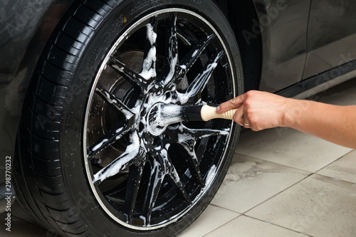 Pinturas sobre lienzo  A male worker washes a black car with a special brush for cast wheels and scrubs the surface to shine in a vehicle detailing workshop