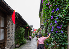 Small Lane On Laomen East Pedestrian Street, Nanjing, Jiangsu, China, With Historic Buildings On Two Side. A Girl Takes Photos Of Purple Morning Glories On Wall.