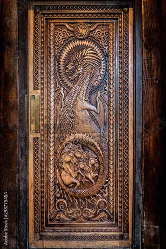BALLINTOY HARBOUR, NORTHERN IRELAND, DECEMBER 20, 2018: Magnificent carved door with dragons and Dothraki horses, made with wood from the Dark Hedges Canvas Print