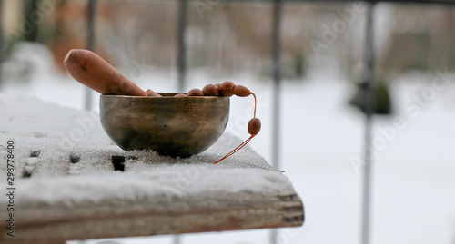Tibetan singing bowl with its hammer on wooden table, close-up Canvas Print