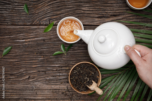 Canvas Prints Tea Hand pour hot steaming tea into cup from teapot and dried herb tea on the wooden table empty space creative flat lay, Organic product from the nature for healthy with traditional style