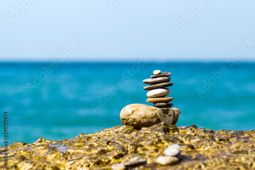 Poster de jardin Zen pierres a sable paradise coast, a pyramid of smooth sea stones on a background of the sea