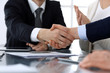 Business people shaking hands after contract signing in modern office. Unknown businessman with colleagues at meeting or negotiation. Teamwork, partnership and handshake concept