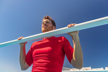 Fit Man Training Arched Back Pull Up On Bar Gym Workout Shoulder Exercise. Male Athlete Working Out Outside.