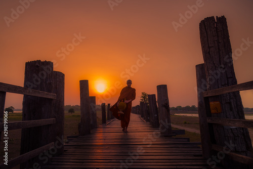 Asian  monk buddha religion Walking alms in early morning for Buddhist Offer food to monk at U-bein bridge , Myanmar Wallpaper Mural