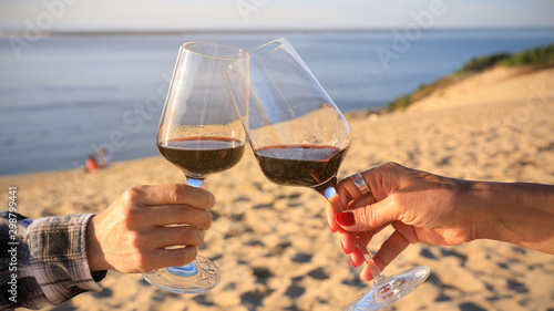 Foto auf Leinwand Alkohol close up hand of romantic couple or friendship which happy moment relaxing ,red,wineglass,celebration on the beach