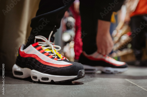 Side view of bright sneakers with black and red stripes on crop person bending t Obraz na płótnie