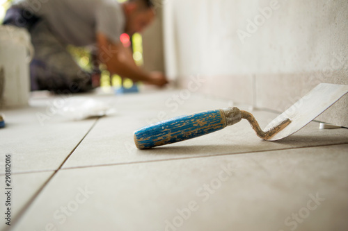 Fotografie, Obraz  Trowel is on the floor and behind is a worker gluing ceramic tiles