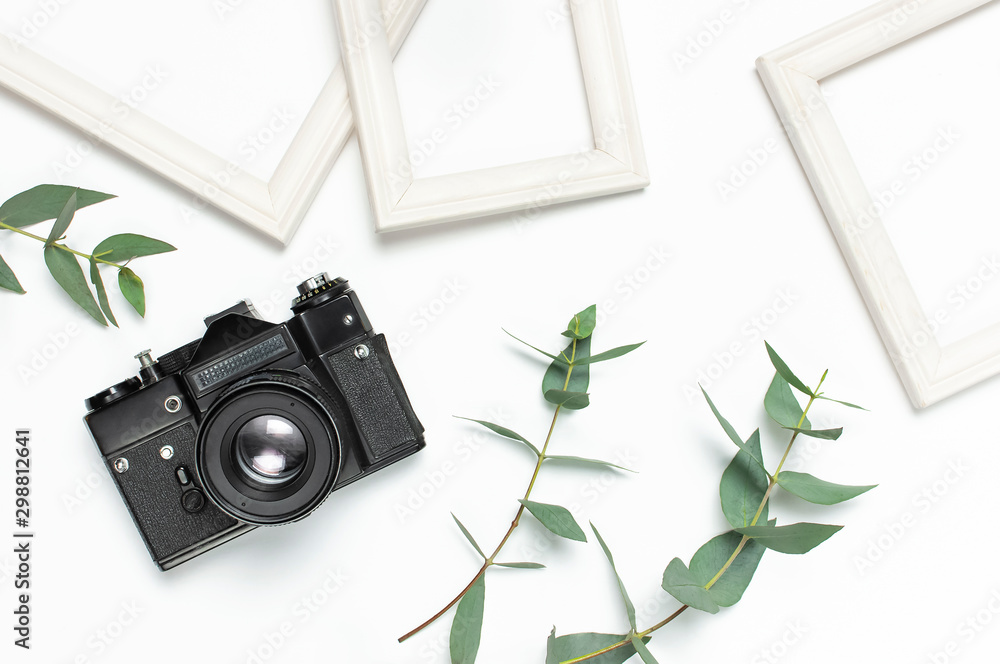 Fototapeta White photo frame, old retro photo camera and green eucalyptus leaves on white background. Flat lay top view copy space. Stylish minimal composition, artwork mockup, picture frame, home decoration